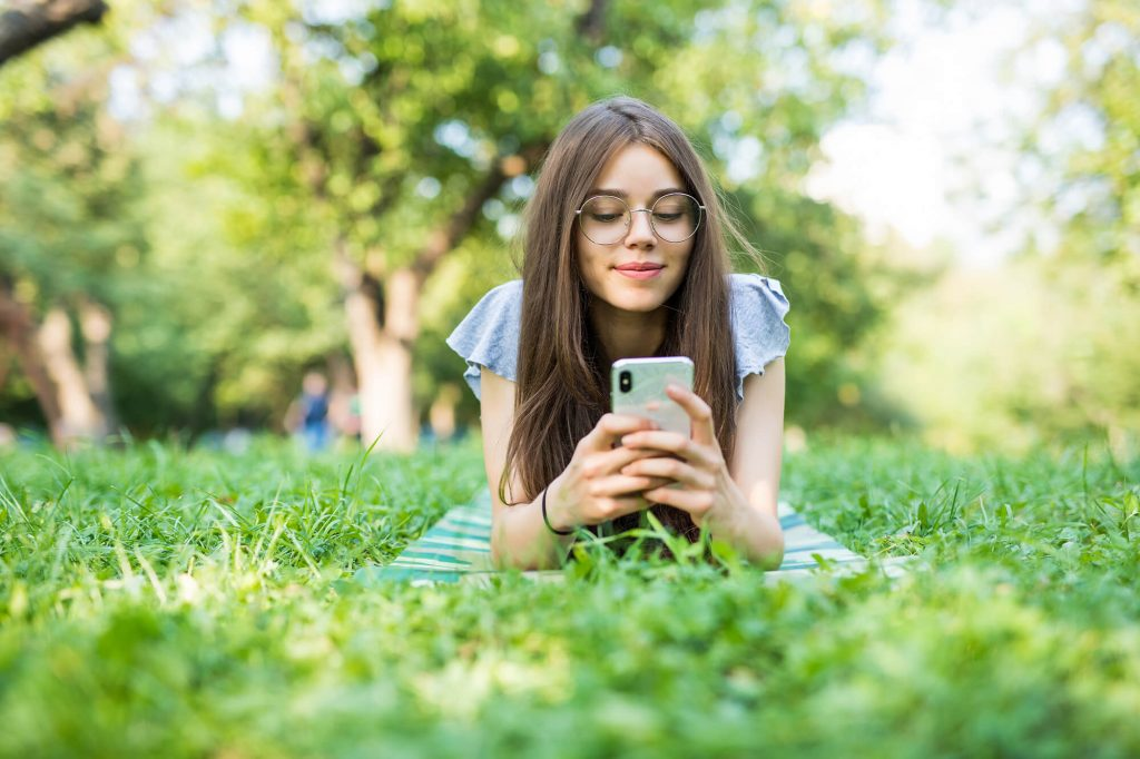 The Beautiful Woman Reading Phone Message On Grass